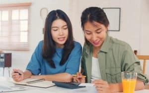 Women sitting looking at finances on paper before getting a vehicle loan