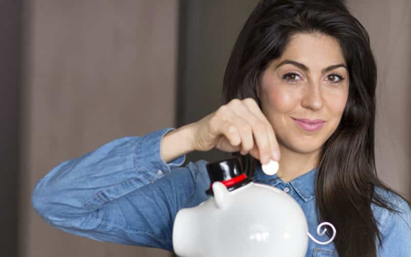 Young Woman Putting Coin into Piggy Bank