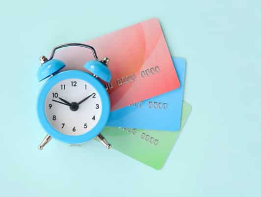 Alarm Clock in front of credit cards