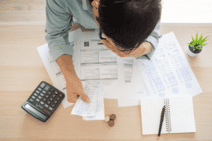 Man Calculating Financials with paperwork and calculator
