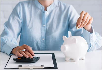 Man calculating financials and putting coin in piggy bank