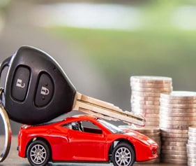 Remote control car and car remote next to coin stack