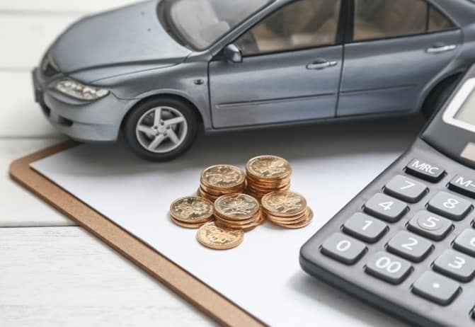 remote control car next to stack of coins on clipboard