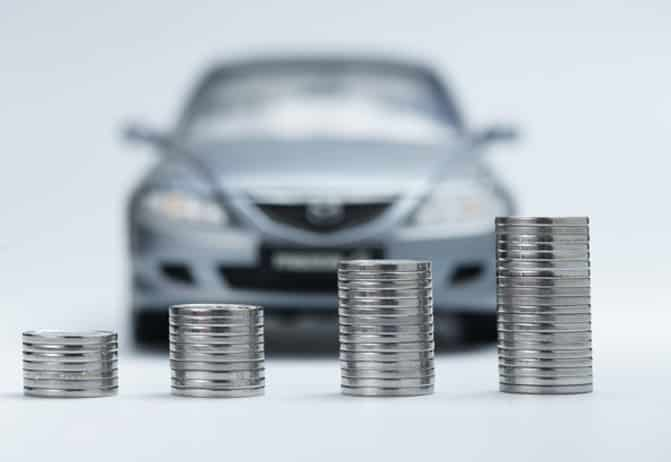 Coins stackd in front of car for vehicle loan