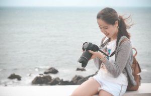 woman sitting on beach with camera smiling
