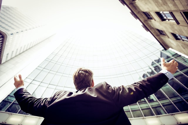 man looking up at tall buildings resembling new business opportunities