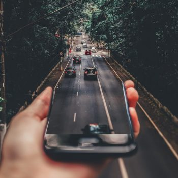 holding phone with car photo to symbolise car and vehicle loan
